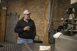Jeremy Garchow, of Chicago, checks out old coffee roasting equipment at new roastery for Passion House Coffee and Roasters in East Garfield Park. | ALEX ROGALS/Staff Photographer