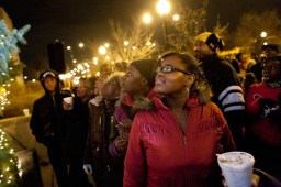 Austin kids, including Kamilah Grissett, look up at the tree as the lights are turned on outside the 15th District Police Station in Austin.