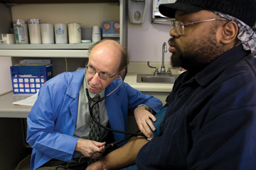Healing time: Dr. Jon Beran checks a patient's blood pressure at Circle Family Healthcare Network, 5002 W. Madison St. Beran has been with Circle from its beginning in 1977.File 2012