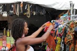 A woman looks at a rack of colorful dresses and skirts. (ASHLEY LISENBY/digital editor)