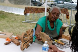 An craftsman leads a wood carving workshop with festival attendees. (ASHLEY LISENBY/digital editor)