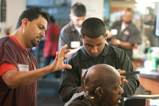 """Instructor Armondo Peguerd guides Johnny Negron through a straight-razor shave. Rather than use the artificial haircut heads common in many barber schools, students train on live """"models"""" who get their cuts for free. (David Pierini/staff photographer)"""
