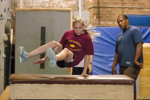Annaliese Miller, of Oak Park, leaps over an obstacle at LivFit Gym in Forest Park during a parkour class taught by Paul Canada.