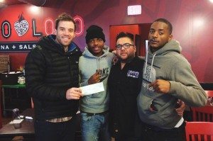 Matt Jones, Antwon Love and Tevin Russell (left) celebrate a sponsorship check they received for their church basketball team. But the friends say they had a run-in with Chicago police last year that was unwarranted. (Courtesy AustinTalks)