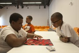 Jeremiah, 12, and Amari, 7, play checkers at By the Hand as part of a summer enrichment camp. (David Pierini/staff photographer)