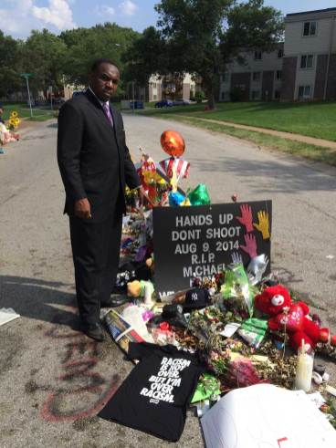 Time passed: Austin's Rev. Ira Acree stands at the site of Michael Brown's shooting by a white police officer in Ferguson Mo. Aug. 9. (Courtesy Rev. Ira Acree)