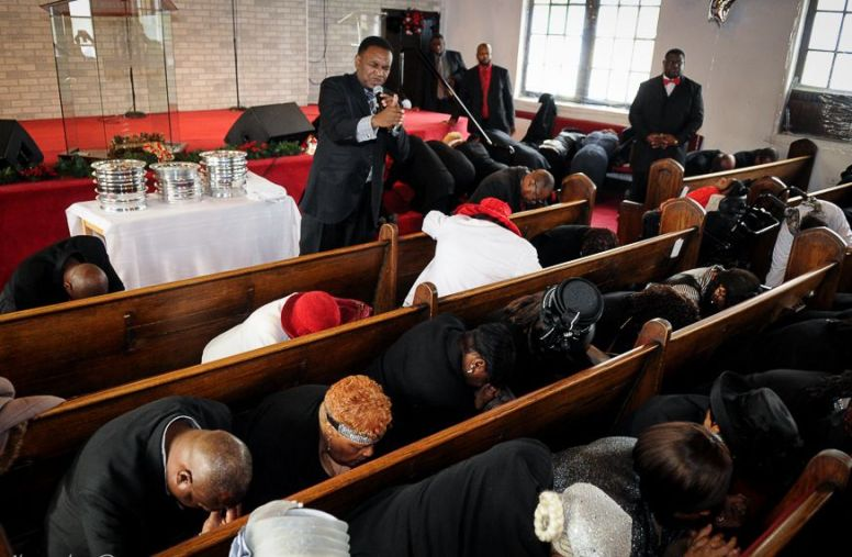 On bended knees with heads bowed, the Greater St. John Bible Church congregation prayed for the families of police shooting victims Michael Brown of Ferguson Missouri and Eric Garner of Staten Island New York following their Sunday morning church service Dec 7. (Dwayne Truss/CONTRIBUTOR)