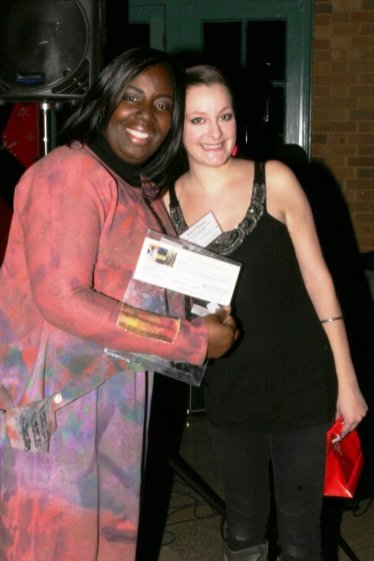 D'Lana O'Neil of Local-Motions (left) poses with her prize, tickets to a performance at Dominican Performing Arts Center