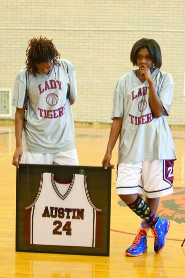 Amari Williams and Star Jones, members of the Austin High School girl's basketball team, hold the jersey of Ashley Hardmon, a 2012 graduate who was shot to death July. 2 2014. (David Pierini/staff photographer)