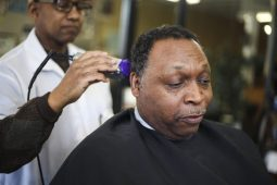 Curtis Brown, 48, above, gets a trim at the barber shop. (Chandler West/Staff Photographer)