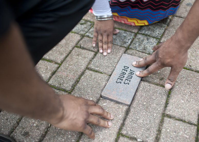 Denna, Malcolm and Corey Deanes lay a brick in remembrance of their father, James Deanes. The longtime education activist, who passed away last year, was posthumously honored by the Austin Green Team during a ceremony last Sat., May 16, at Heroes Park, located at the corner of Washington and Laramie. Deanes was honored along with Michael Scott, Sr., Clarence Campbell and Clarence Langworthy. (William Carmago/Staff Photographer)