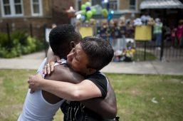 Elizabeth Ramirez embraces Antonio Brown, whose son, Amari Brown, 7, was fatally shot in the chest on July 4. On July 6, Ramirez offered to hold a vigil in Amari's honor. William Camargo/Staff.