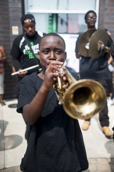 STATUE UNVEILING: Isaac Allen blows his trumpet during Mandela Road's one-year anniversary ceremony on Sat. July 18. | WILLIAM CAMARGO/Staff Photographer