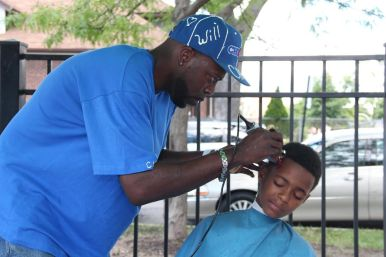 A young West Side resident receives a free haircut during Greater St. John Bible Church's annual Austin Community Fest on Aug. 13. The fest, held on the grounds of Ella Flagg Young School, featured vendors, pony rides, food, music and 0,000 in college scholarships to area young people. | Courtesy Greater St. John Bible Church