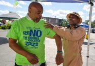 Retired Army Sgt. Major Reginald Ferguson, left, gets help putting his shirt on from Marine Corps veteran Dion Bush on Saturday, July 29, 2017 during the 29th annual Say No To Drugs and Violence Parade and Back to School Rally in Chicago's Austin neighborhood. | Alexa Rogals/Staff Photographer