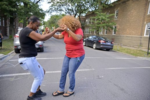Austin community leader Zerlina Smith, right, dances with a neighbor on Wednesday, Aug. 30, 2017, during a remembrance celebration and barbecue for Elijah Sims at the corner of Lotus Avenue and Quincy Street in Chicago's Austin neighborhood. | ALEA ROGALS/Staff Photographer