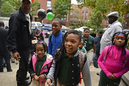 Students walk up the steps are a greeted and cheered on by fathers of the students on Wednesday, Sept. 13, 2017, before the start of the school day at Catalyst Circle Rock Charter School in Chicago's Austin neighborhood.