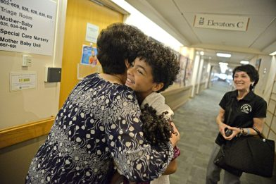 Registered nurse Vilma Duran, left, hugs Aidan Jane Millar-Nicholson last Wednesday at the West Suburban Medical Center in Oak Park. Duran was one of the nurses who cared for Millar-Nicholson when she first arrived to the medical center. Aidan Jane Millar-Nicholson walks with her parents to see newborns. | ALEXA ROGALS/Staff Photographer