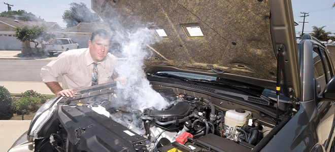 A man inspecting an overheating car engine