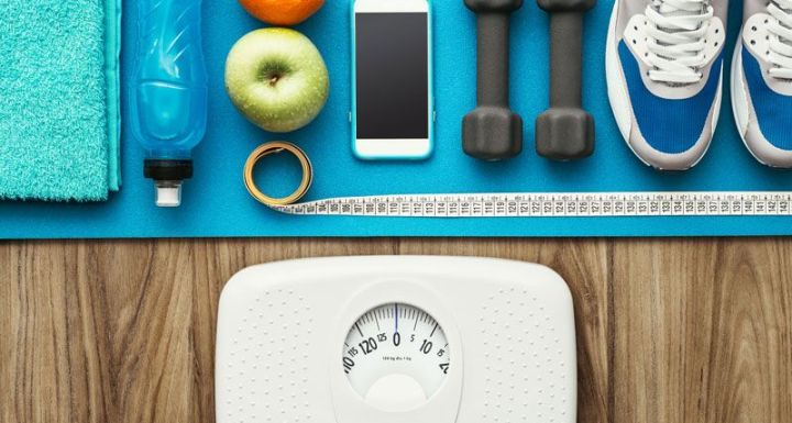 scale surrounded by exercise equipment and water bottle