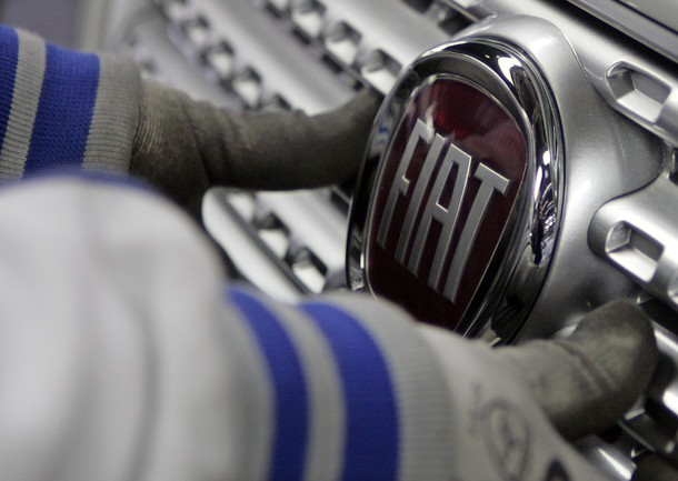 Worker adjusts logo on new Fiat Punto at Fiat factory assembly line in Kragujevac