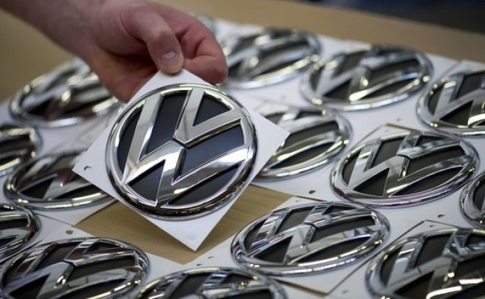 A Volkswagen employee picks up a logo to