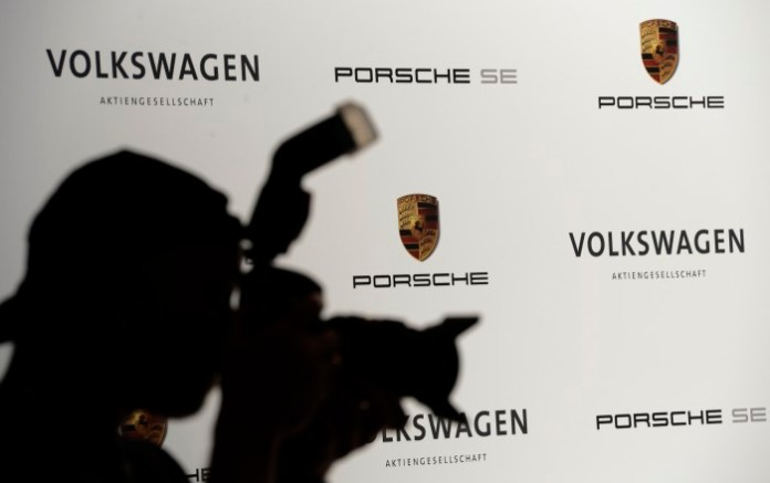 A photographer is silhouetted during a press conference of German carmakers Volkswagen and Porsche in Wolfsburg