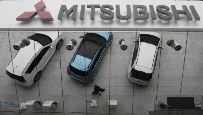 Mitsubishi Motors Corp's vehicles are reflected on an external wall at the company headquarters in Tokyo