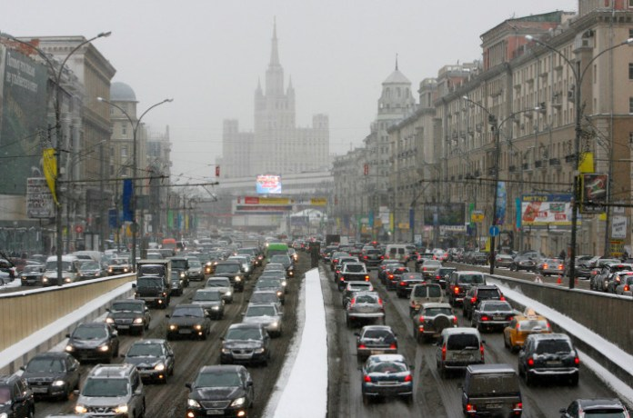 Cars move under a snowfall in central Moscow
