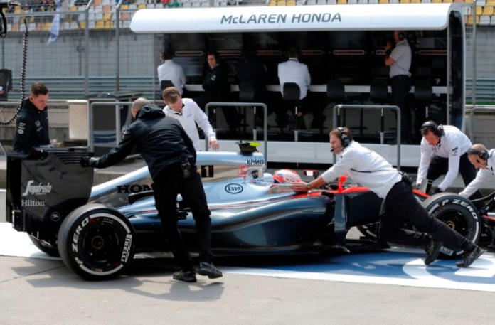 Jenson Button is pushed back in to the garage.