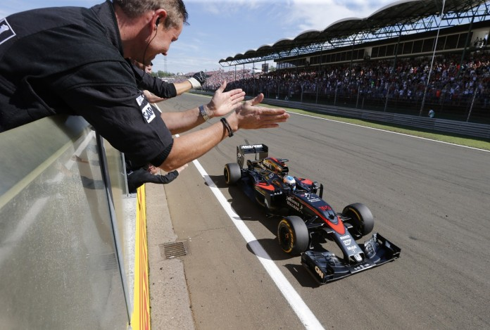 Team members celebrate Fernando Alonso's 5th place finish.