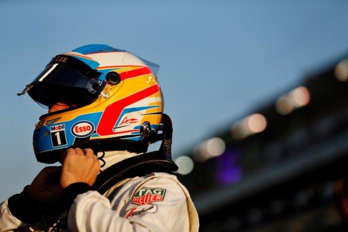 Fernando Alonso puts on his helmet.