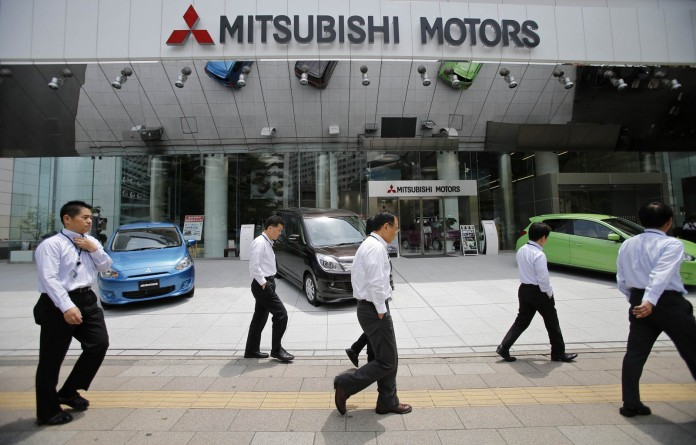 Men walk in front of Mitsubishi Motors Corp's headquarters in Tokyo