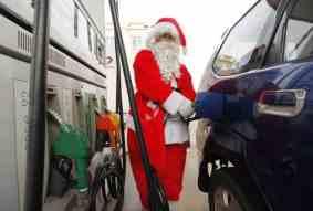 Papai Noel abastecendo seu carro junto a bomba de combustível