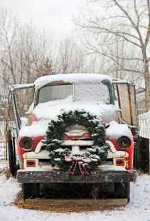 Caminhão Chevrolet antigo e abandonado, coberto de neve e com uma grande guirlanda de Natal enfeitando-o na dianteira