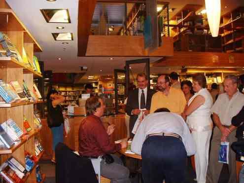 Destaque para Maria Aparecida Prófito Pucci. autora; de pé, de roupa branca, ao lado de seu marido com camisa amarela