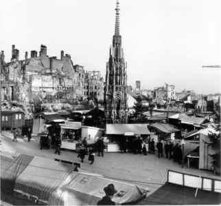 No Natal de 1946 o Schöner Brunnen já liberado da proteção de concreto fazendo parte do cenário do Christkindelmarkt; ao fundo o testemunho da destruição