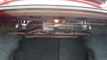 Molas de torção para sustentar a tampa do porta-malas aberta; atrás, o amplificador do subwoofer