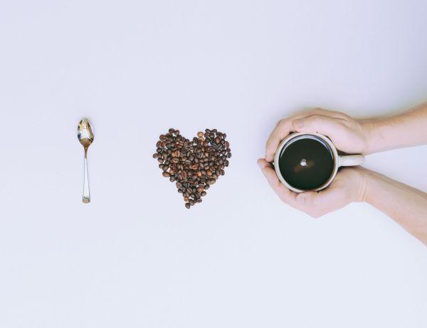 Hände halten eine Tasse Kaffee in der hand, in der Mitte ist ein Herz aus Kaffeebohnen, rechts ein silbernen Löffel