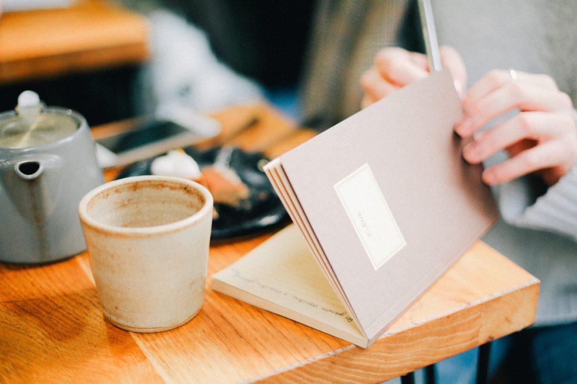 Eine frau sitzt an einem Tisch und vermeidet Stress durch Planung, im Hintergrund stehen eine Kanne und ein Kaffebecher