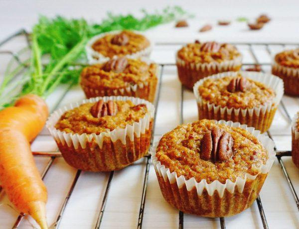 Karotten-Nuss-Muffins mit Karotten und Grün im Hintergrund