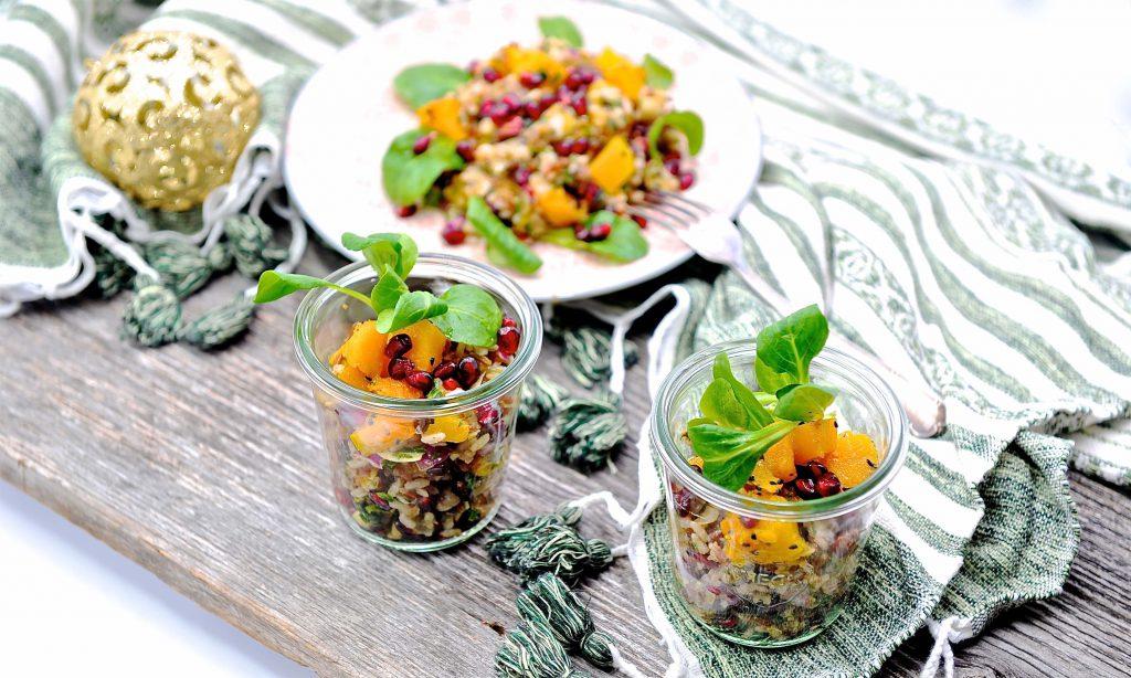 Weihnachtlicher Granatapfel-Reis-Salat in Gläsern. Im Hintergrund eine goldene Kugel.