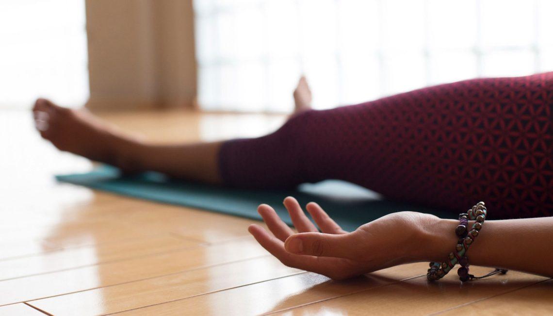 Yoga Nidra Mensch praktiziert im Liegen.