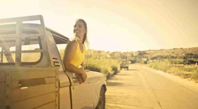 woman wearing yellow shirt inside pickup truck. Hybrid pickup trucks
