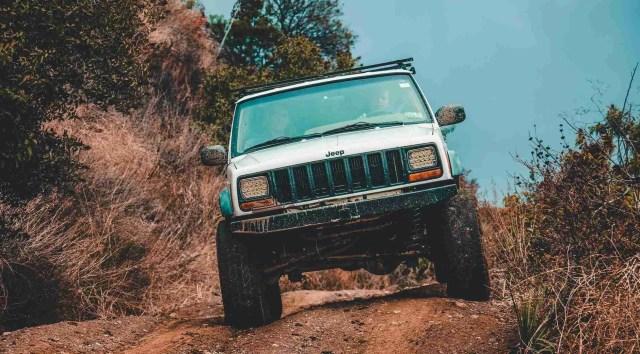 white jeep grand cherokee zj suv cruising down the road. Best overland vehicle under $5000