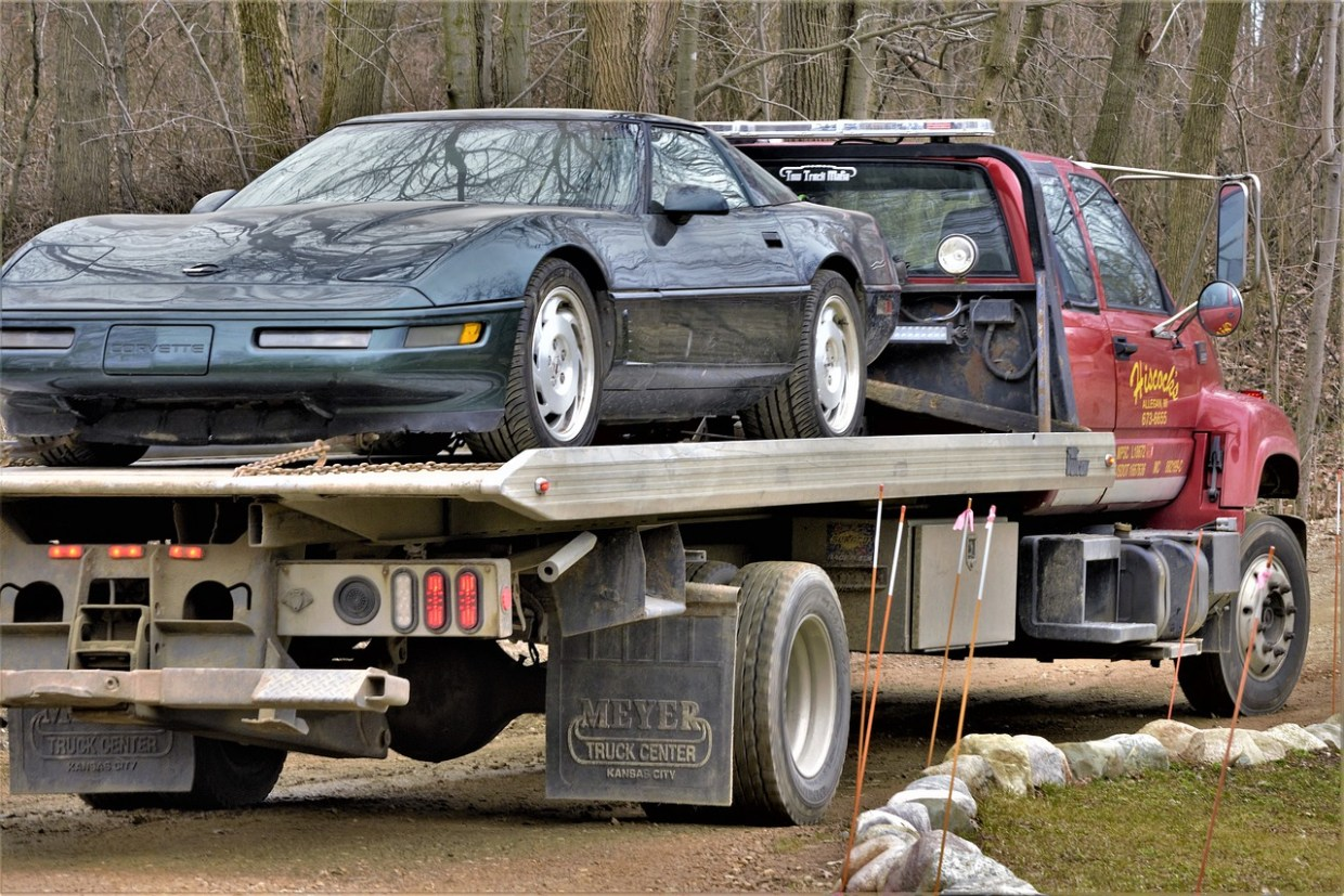 A car being hauled away by a truck