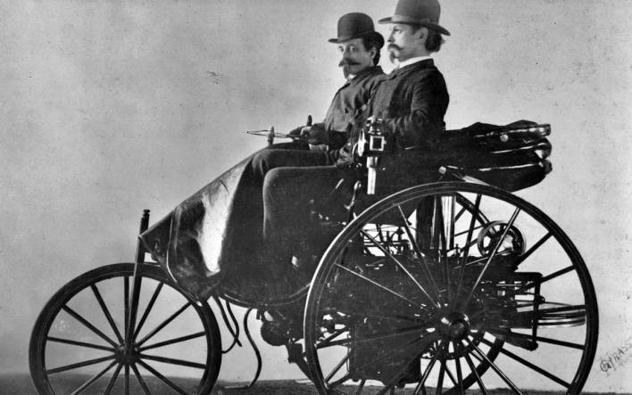 Carl Benz conduciendo su invento, acompañado de un colaborador