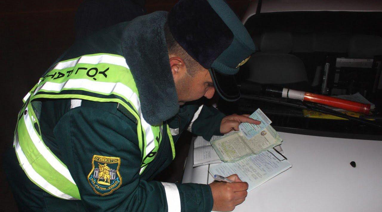 Инспектор ДПС ГАИ оформляет протокол об административном правонарушении в Ташкенте, Узбекистан