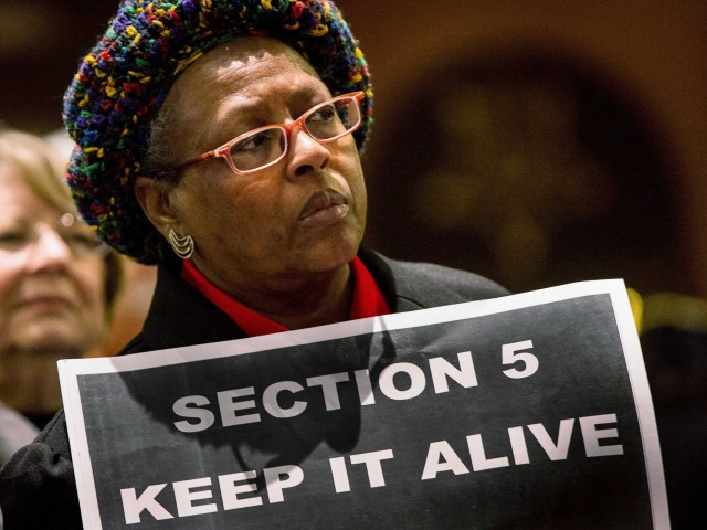 Woman holds sign 'Section 5 Keep it alive' as Supreme Court hears Voting Rights.