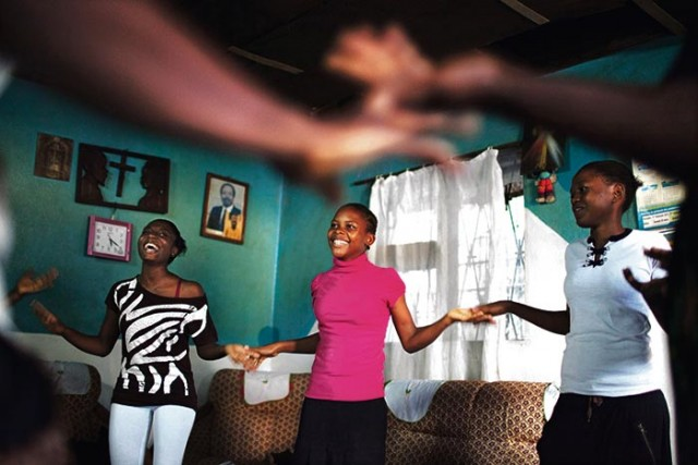 Girls play clapping game during a weekly education session about breast ironing and rape by survivor of breast ironing Ndjessa at Ndjessa's family home in Douala